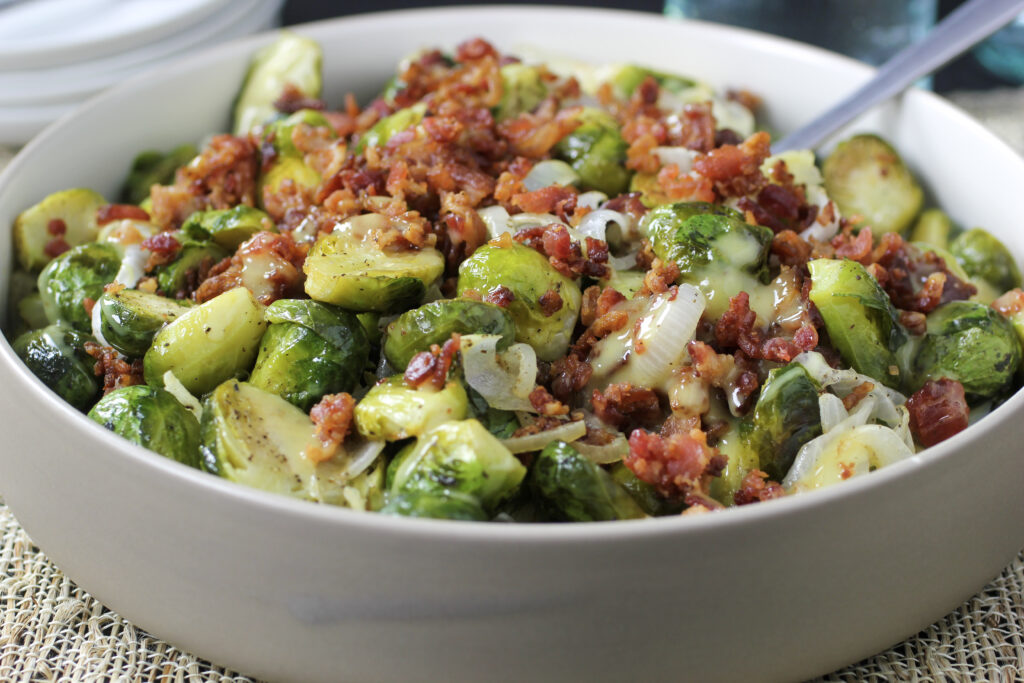 brussels sprouts with onion, bacon and dijon dressing in bowl with spoon.  a perfect thanksgiving recipe