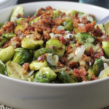 brussels sprouts with onion, bacon and dijon dressing in bowl with spoon