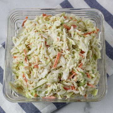 classic coleslaw in square bowl with striped tea towel