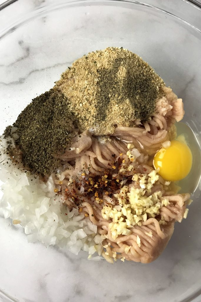 ground chicken, bread crumbs, egg, onion, garlic and spices in glass bowl