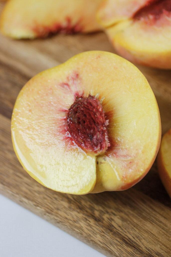 half of a fresh peach on cutting board