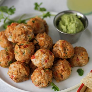 southest chicken meatballs on plate with avocado cream sauce for dipping