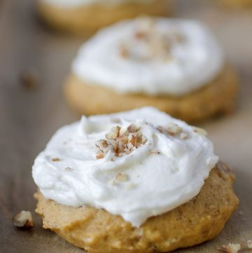 pumpkin cookies with icing and nuts on cookie sheet with parchment paper