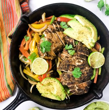 bell peppers, fajitas chicken, lime, avocado and cilantro in black skillet with dish towel