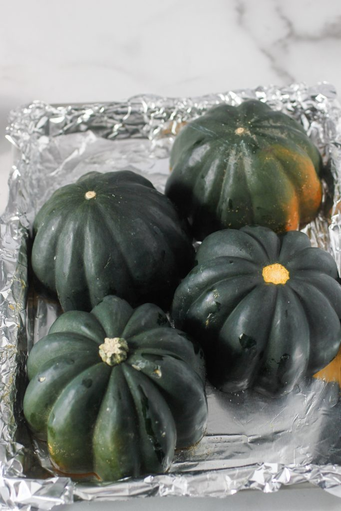 acorn squash upside down going into oven to bake on a baking sheet covered with foil,