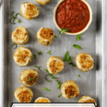 meatballs on cookie sheet with a bowl of classic marinara and a sprinkle of fresh basil