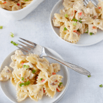 ranch bacon chicken pasta on two white plates with fork