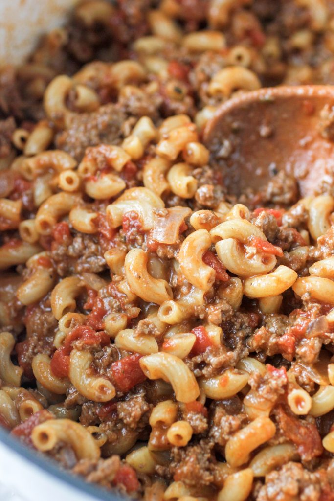 ground beef and noodles in dutch oven with a wooden spoon